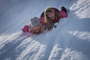 Kinder lieben es, sich im Schnee zu wälzen. Mit guter Bekleidung bleiben sie dabei sogar trocken.